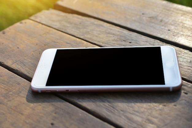 Telefone inteligente móvel está na mesa de madeira