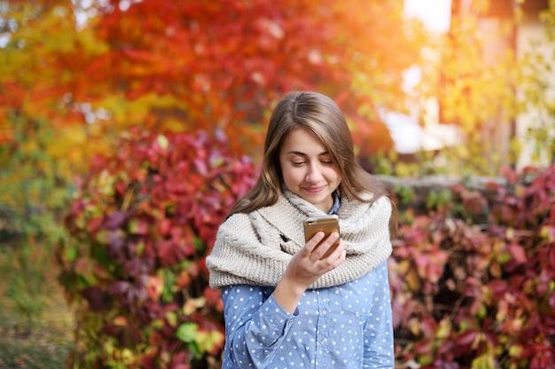 Telefone inteligente mulher de outono escrevendo sms no celular no outono