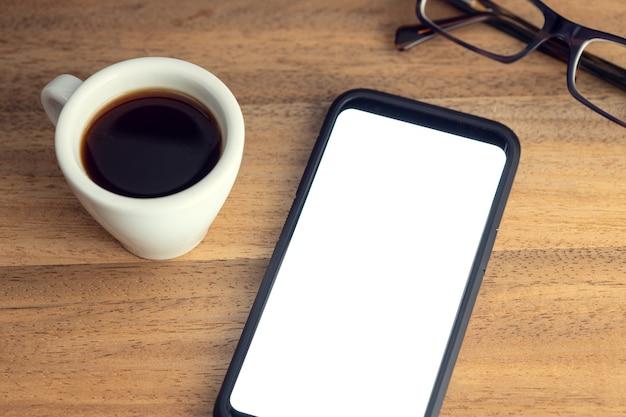 Telefone inteligente na mesa com tela branca, óculos e xícara de café na mesa de madeira