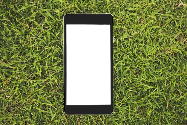 Telefone inteligente preto com tela em branco na grama