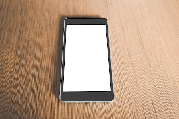 Telefone inteligente preto com tela em branco na mesa de madeira. conceito de tecnologia.