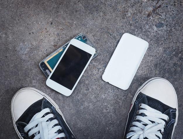 Telefone inteligente quebrado no piso de concreto entre os sapatos de tênis do proprietário