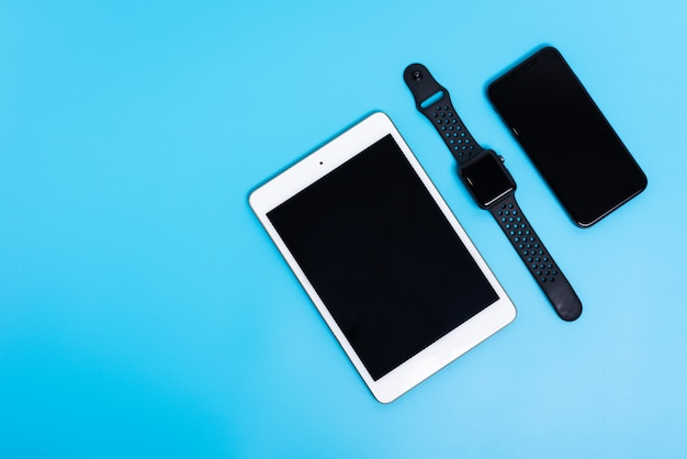 Telefone inteligente, relógio inteligente e tablet em fundo azul celeste, flat lay