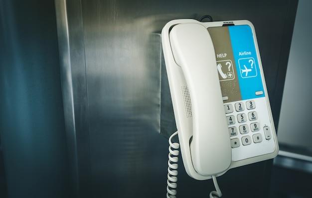 Telefone interno que pendura em um polo no aeroporto internacional para o auxílio e a ajuda.