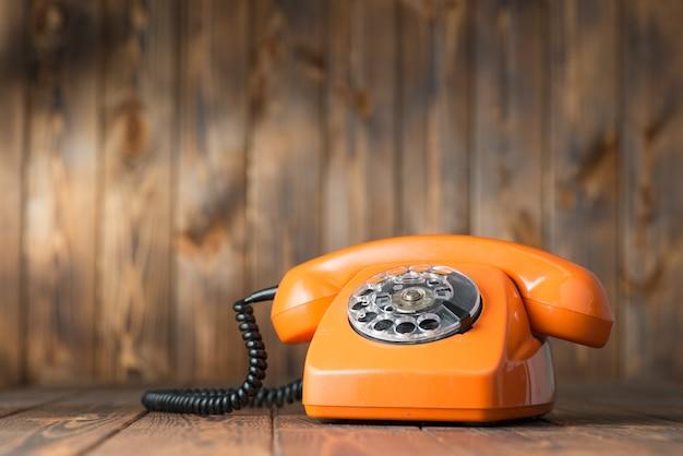 Telefone laranja vintage em uma mesa de madeira