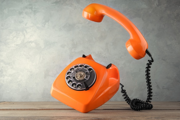Telefone laranja vintage levitar sobre a mesa Foto Premium