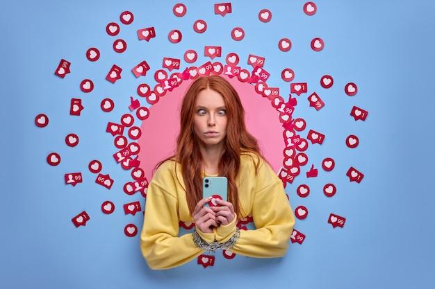 Telefone móvel acorrentado às mãos de mulher, dependência de internet. mídia social. muitas curtidas na parede azul