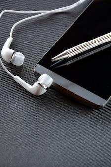Telefone móvel com caneta e fones de ouvido