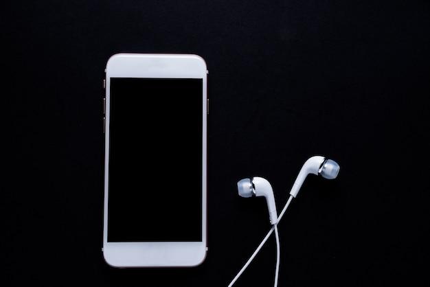 Telefone móvel com fone de ouvido no fundo escuro