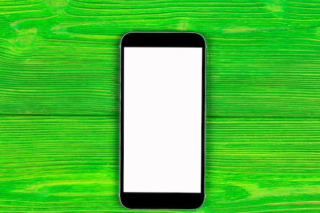 Telefone móvel com simulação de tela em branco isolada no fundo da mesa de madeira verde. smartphone na mesa de madeira. smartfone branco