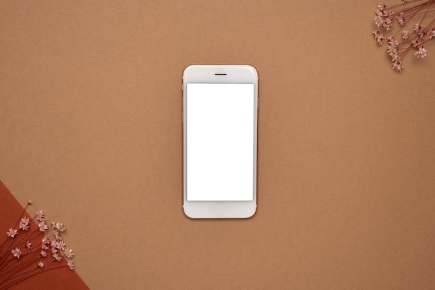 Telefone móvel com tela branca e galho e pedra de flor seca em um fundo marrom claro. tendência, conceito mínimo com vista superior do copyspace