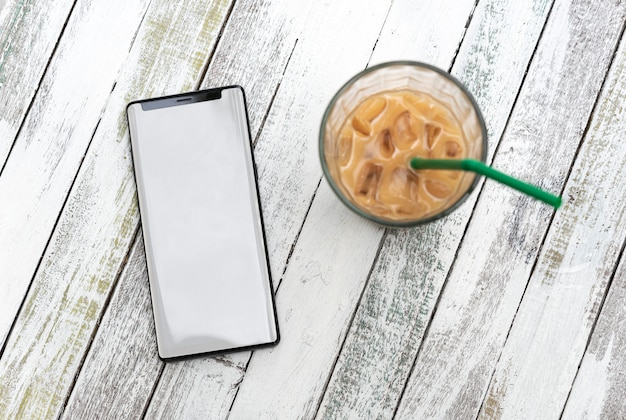Telefone móvel com tela em branco e xícara de café na mesa de madeira no café.