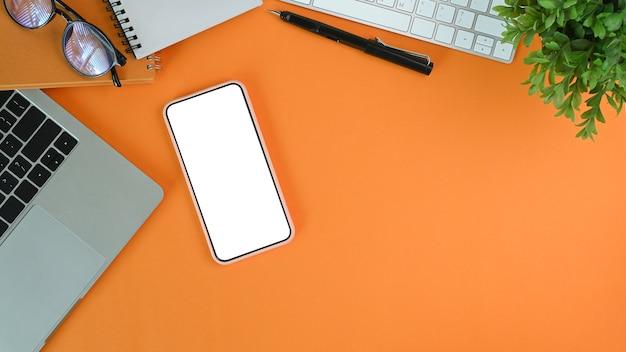 Telefone móvel com tela em branco, laptop, planta da casa, óculos e fundo laranja do caderno.