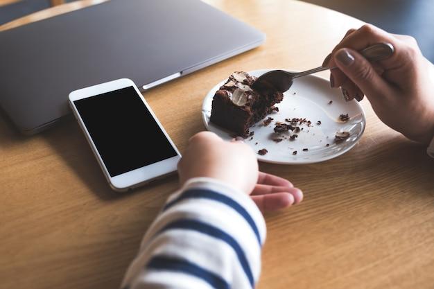 Telefone móvel com tela preta em branco ao lado do laptop com uma mulher comendo bolo brownie
