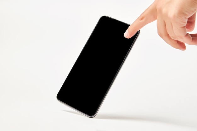 Telefone móvel com tela preta em fundo branco com espaço de cópia. tela em branco da maquete do smartphone isolada com traçado de recorte