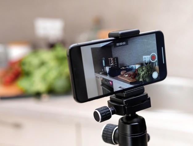 Telefone móvel de close-up na gravação de tripé