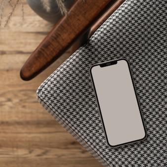 Telefone móvel de tela em branco na cadeira vintage. layout plano, vista de cima, blog minimalista, site