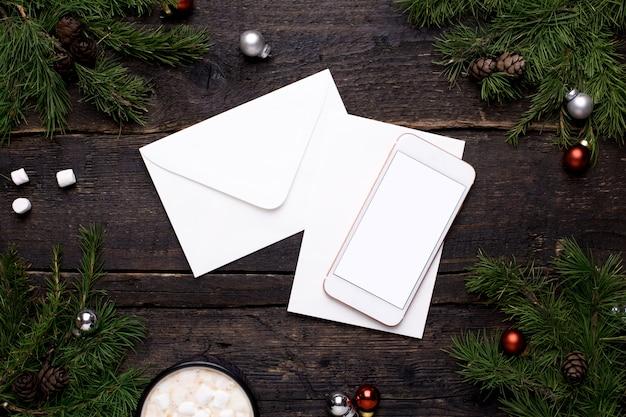 Telefone móvel e cartão postal em uma mesa de madeira com uma árvore de natal