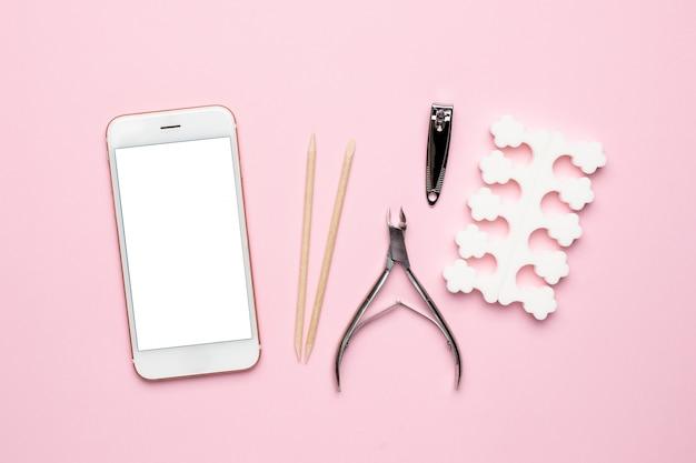 Telefone móvel e ferramentas de manicure e pedicure em rosa
