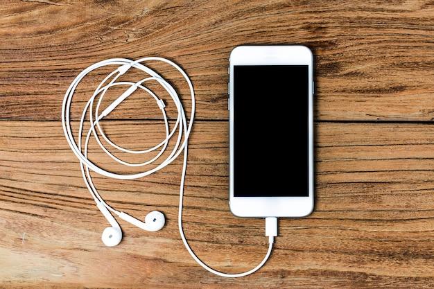 Telefone móvel e fones de ouvido no fundo de madeira
