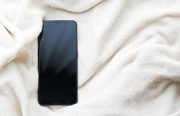 Telefone móvel em cobertor branco no inverno como maquete de plano de fundo de smartphone de fundo de ...