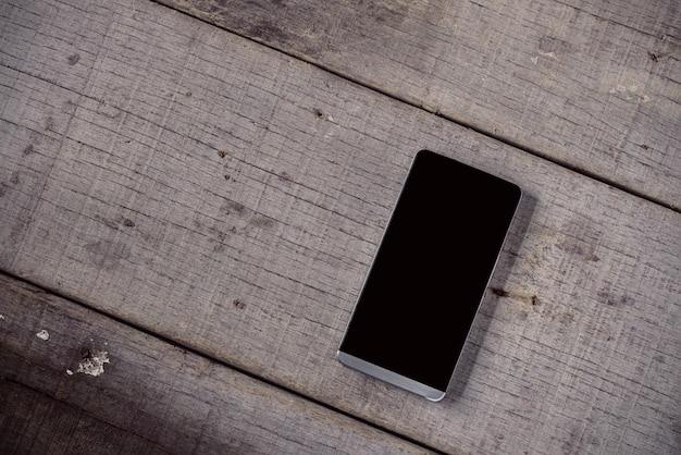 Telefone móvel em madeira velha.