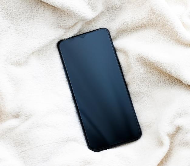 Telefone móvel em tecido macio de luxo em maquete de flatlay de smartphone de inverno como modelo de aplicativo e marca mar ...