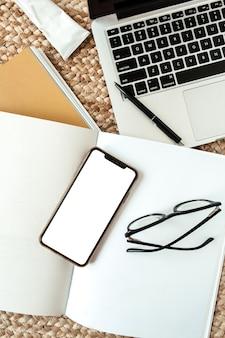 Telefone móvel inteligente com espaço vazio da cópia, laptop, óculos. área de trabalho da mesa da mesa do escritório em casa com vista superior plana lay.