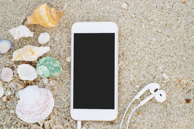 Telefone móvel inteligente com tela vazia e fone de ouvido deitado na areia do mar da praia com conchas. vista superior com espaço de cópia