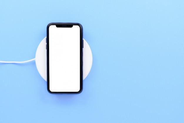 Telefone móvel preto colocar no carregador sem fio branco