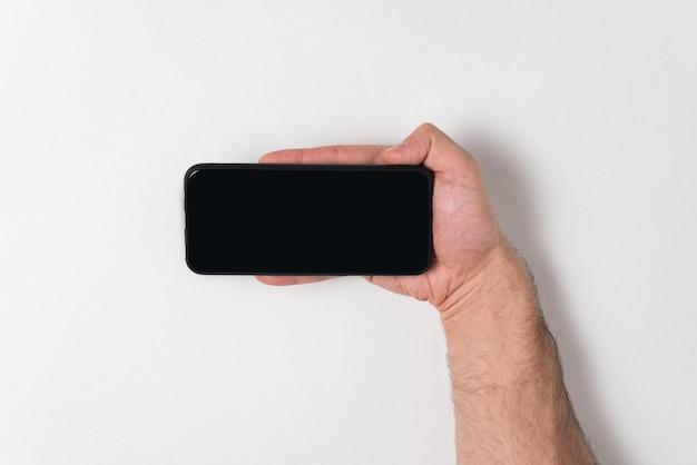 Telefone na mão masculina em fundo branco. visor em branco preto. copiar maquete de espaço