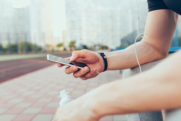 Telefone na mão musculosa de um cara sentado na cidade pela manhã. ele segura uma garrafa de água e fones de ouvido.