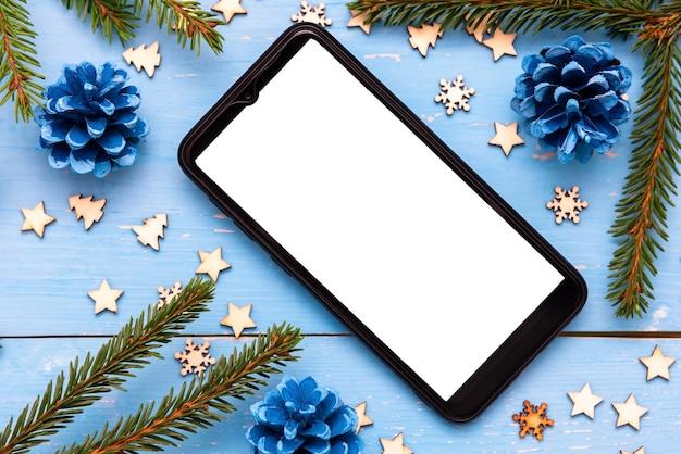 Telefone na mesa de natal com árvores de natal.