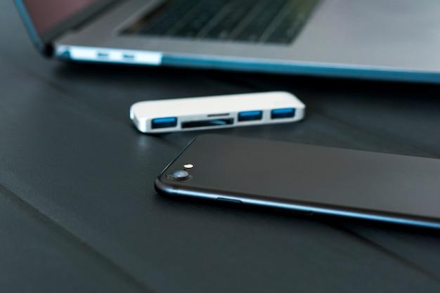 Telefone preto coloca na mesa preta perto de hub tipo c usb e laptop