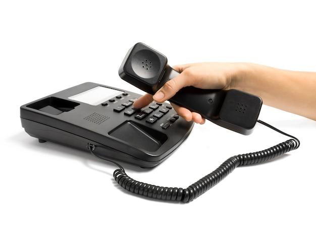 Telefone preto do escritório com a mão isolada no branco