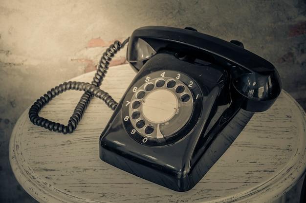Telefone preto vintage no antigo fundo de paredes