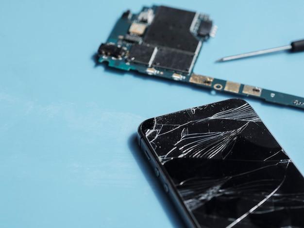 Telefone quebrado e placa de circuito em fundo azul