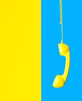 Telefone retro amarelo pendurado no fio espiral no fundo dividido ao meio em azul-celeste e amarelo