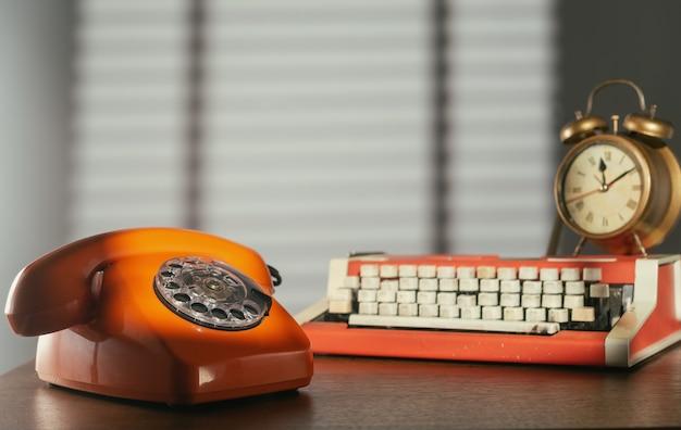 Telefone retro, máquina de escrever e despertador na mesa