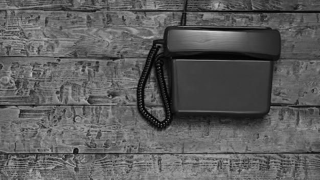 Telefone retro sem a possibilidade de discar em uma mesa de madeira preta