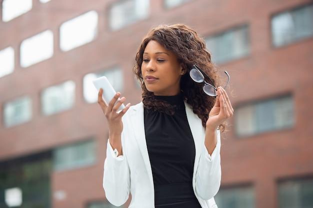 Telefone rolando conversando com empresária afro-americana em traje de escritório sorrindo