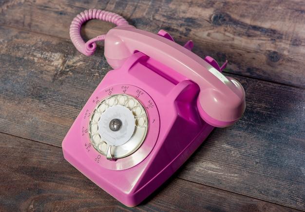 Telefone rotativo rosa retrô na mesa de madeira