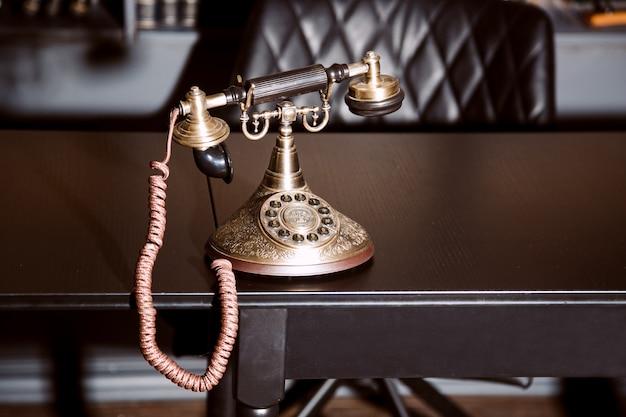 Telefone velho do castiçal da antiguidade do vintage na tabela de funcionamento do negócio que trabalha no passado.