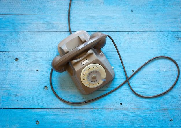 Telefone velho do vintage, em uma superfície de madeira.