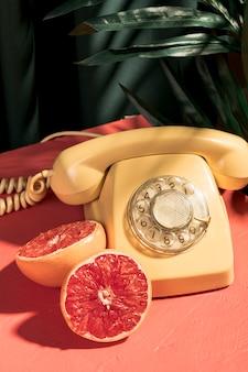 Telefone vintage amarelo ao lado de toranja cortada ao meio