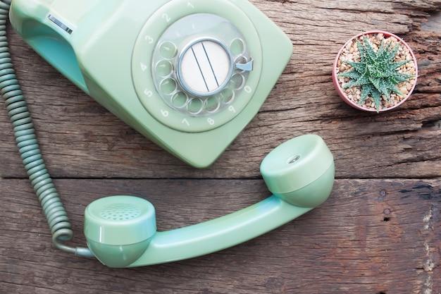 Telefone vintage e planta de cactos na mesa de madeira