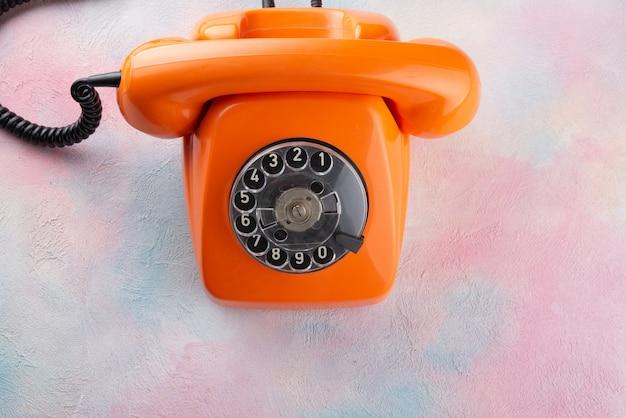 Telefone vintage laranja em uma mesa multicolorida - vista superior