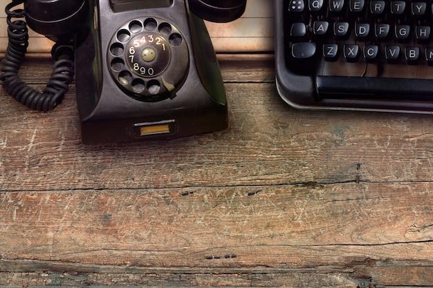 Telefone vintage preto e máquina de escrever no fundo da mesa de madeira