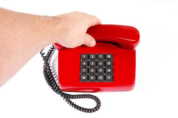 Telefone vintage vermelho com botões e uma mão masculina.