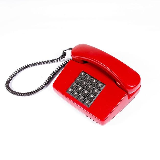 Telefone vintage vermelho com botões em uma superfície isolada branca